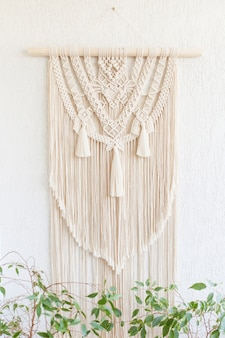 Handmade macrame. 100% cotton wall decoration with wooden hanging on a white wall.