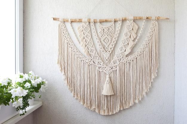 手作りマクラメ。白い壁に掛かっている木の棒が付いている綿100%の壁の装飾。