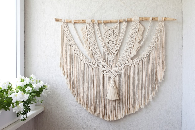 Handmade macrame. 100% cotton wall decoration with wooden stick hanging on a white wall.