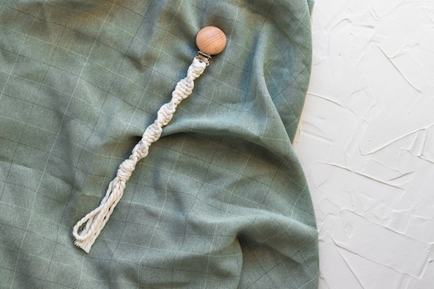 Handmade macrame accessory for newborn, wooden clip holder for pacifier or teether, textile, on white background.