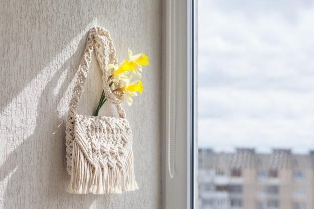Handmade macrame bag  on the light wall.