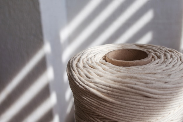 Плетение макраме ручной работы и хлопковые нити крупным планом. катушка для хлопковой пряжи для вязания hobby.
