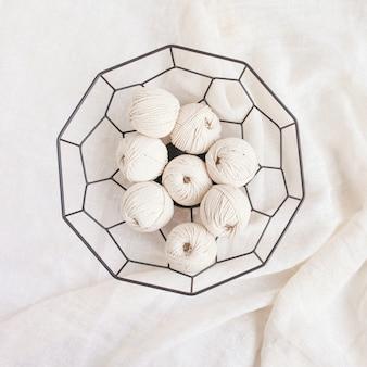 흰색 배경에 바구니에 수제 마크라메 땋기와 면실. 마크라메, 수공예품 현수막 및 광고에 좋은 밝은 이미지입니다. 공간을 복사합니다. 평면도