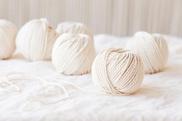 白い背景に手作りのマクラメ編みと綿の糸。マクラメや手工芸品のバナーや広告に適した明るい画像。コピースペース