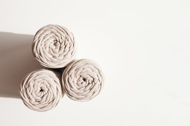 Плетение макраме ручной работы и укладка натуральных хлопковых ниток на белом фоне с тенями