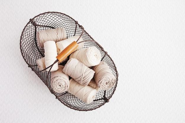 Handmade macrame braiding and cotton threads in basket
