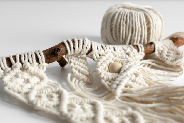 Handmade macrame braiding and cotton threads on rustic wooden stick
