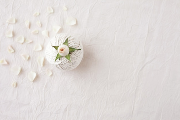 Handmade macrame braiding and cotton threads with rose flower on white textured background, top view
