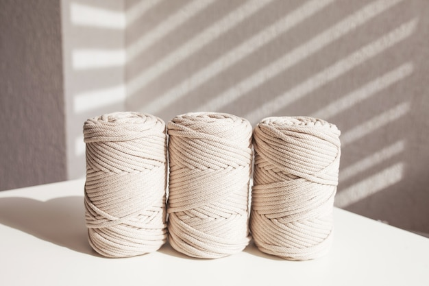 Handmade macrame braiding and natural cotton threads stack on a white background with shadows