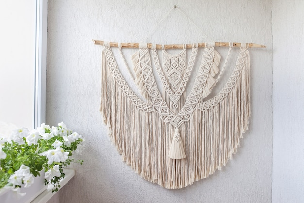 Handmade macrame decoration with wooden stick hanging on a white wall