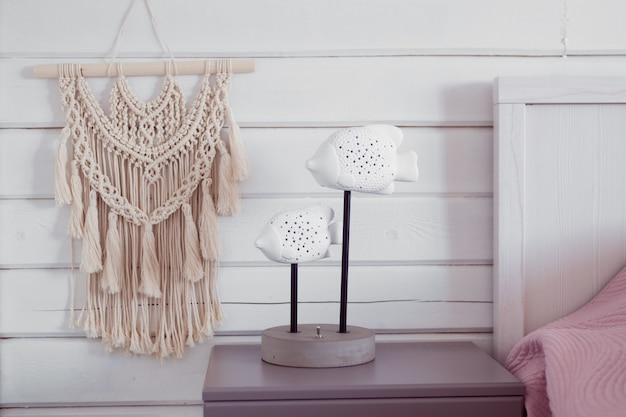 Handmade macrame panel on wooden wall countryside interior details
