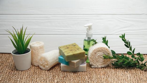 手作りの天然石鹸、洗顔ブラシ、テリー織りのタオル、ヘチマスポンジと緑の植物。健康的なライフスタイルのコンセプトです。美容、スキンケア。バスとスパのアクセサリーのセットです。