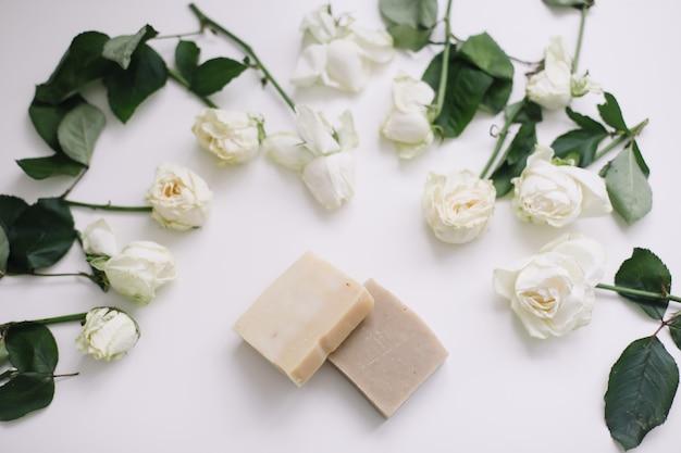 Натуральное мыло ручной работы на белом цветочном фоне. натуральные органические спа косметические продукты на белом