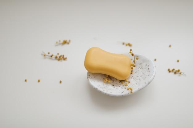 白い花の手作り天然石鹸。石鹸作り。ソープバー。スパ、スキンケア。上から白いテーブルにナチュラルオーガニックスパ化粧品。