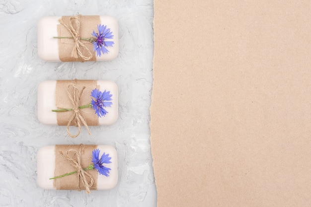 Handmade natural soap set border decorated with craft paper, scourge and blue cornflowers on gray stone backgrouniew flat lay copy space
