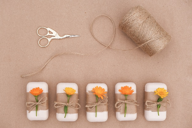Handmade natural soap set decorated with craft paper, orange calendula flowers, skein of twine and scissors .