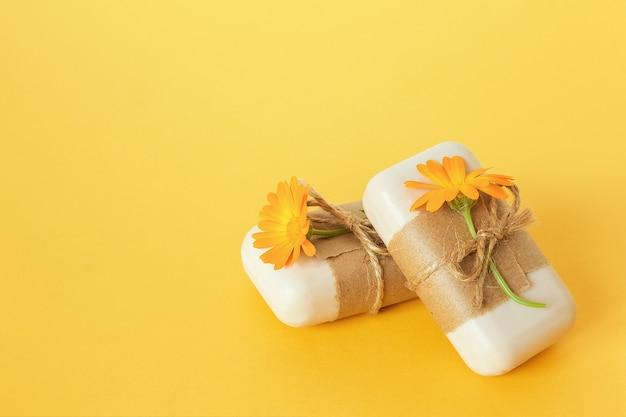 노란색 표면에 공예 종이와 오렌지 금송화 꽃으로 장식 된 수제 천연 비누