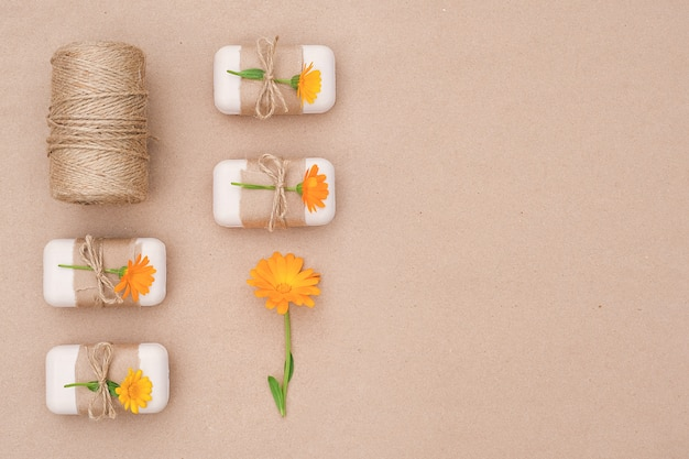 Handmade natural toilet soap set decorated with craft paper, tied with scourge, calendula flowers and skein of twine.