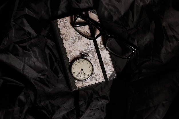 手作りのノート、ヴィンテージ時計、黒い表面に黒いフレームのメガネ