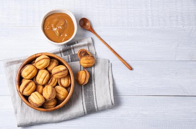 Орехи ручной работы, запеченные с кипяченым молоком и карамелью в миске на белом деревянном столе. вид сверху и плоская планировка