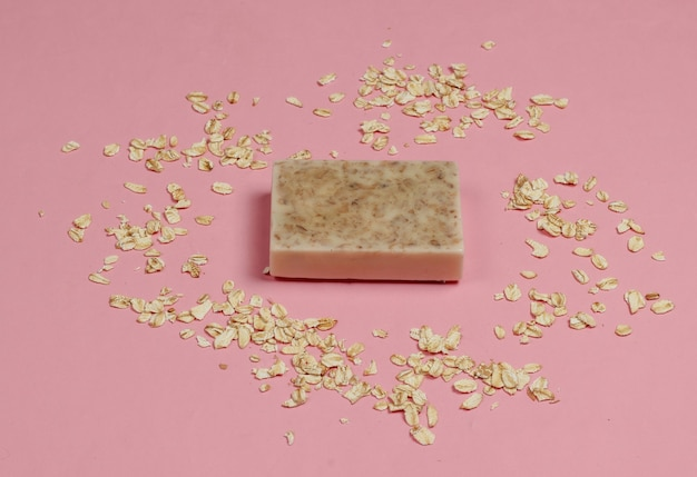 ピンクのパステルカラーの背景に手作りのオートミール石鹸。