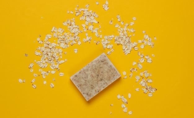 黄色の背景に手作りのオートミール石鹸。上面図
