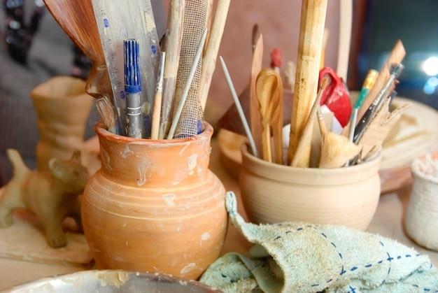 테이블에 연필과 기타 물건이 있는 손으로 만든 오래된 진흙 냄비