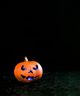 Handmade orange pumpkin in Halloween style with angry carved face illuminated inside