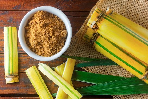 Органический коричневый сахар ручной работы, гранулированный из сахарного тростника в миске на деревянном столе деревенского рафинадного завода. вид сверху
