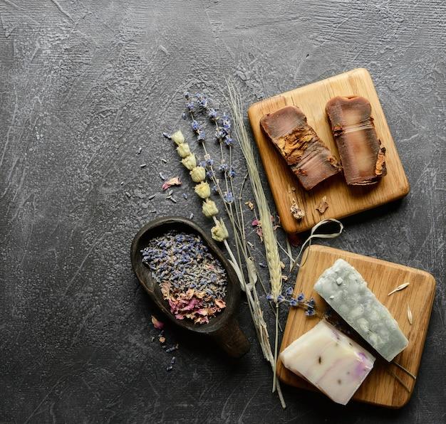 검은 질감의 배경에 말린 허브, 라벤더, 장미 꽃잎이 있는 수제 유기농 비누 oa 나무 스탠드