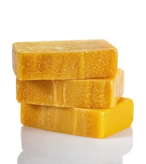 白い背景にオレンジと琥珀色の粉末を使った手作りの有機石鹸。