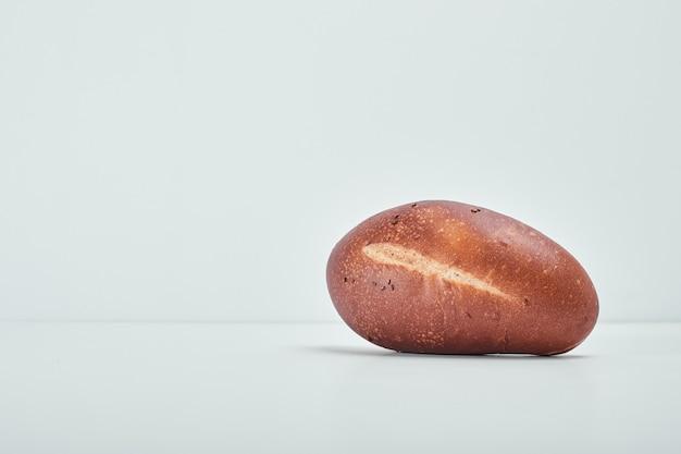 Овальный хлеб ручной работы на сером столе.