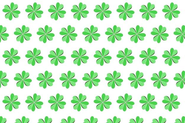 白い壁に4枚の花びらが付いた色付きの緑のシャムロックの葉からの手作りの紙の創造的なパターン。幸せな聖パトリックの日のコンセプト。
