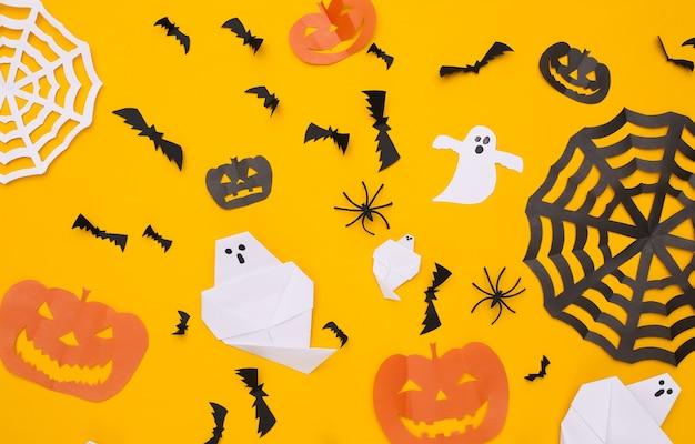 손으로 만든 종이는 노란색 배경에 할로윈 장식을 잘라냅니다. 할로윈 배경입니다. 평면도. 플랫 레이
