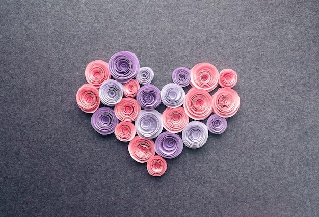 Handmade paper flowers heart on dark felt background
