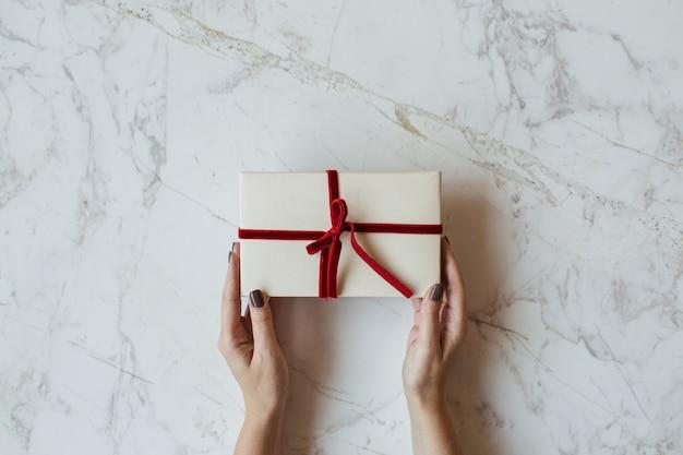 大理石の女性の手で手作りの紙のギフトボックス