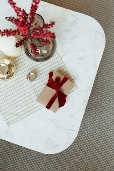 Handmade paper gift box with red ribbon bowtie, red berries in glass vase and decorations on marble table