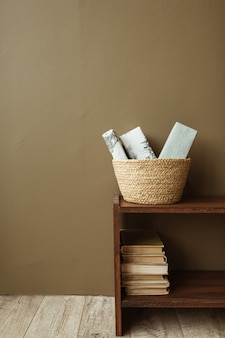 Handmade paper gift boxes in straw basket on wooden stand with books