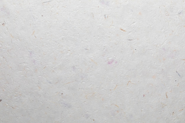 Handmade paper texture with recycled materials, colorful cotton fibers and tree leaves. in delicate shades, pink, purple, mauve, yellow, orange, blue and vanilla.