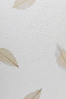Handmade paper texture with recycled materials, tree leaves and cotton fibers.