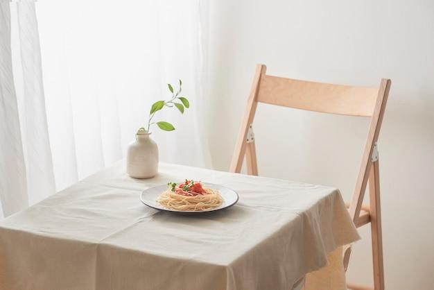 ザルと花とヴィンテージの白いテーブルの上のプレートにラグーソースと手作りパスタ
