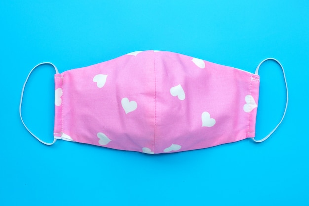 Handmade pink cloth with white hearts mask on blue background. top view