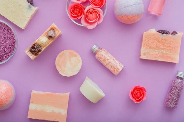 보라색 배경에 수제 분홍색 화려한 비누 스파 목욕 제품 패턴입니다. 폭탄 비즈 목욕 파우더. 바디 스파 스킨 케어 웰니스 스킨케어용 목욕 제품. 아로마 테라피 장미 꽃입니다. 플랫 레이.