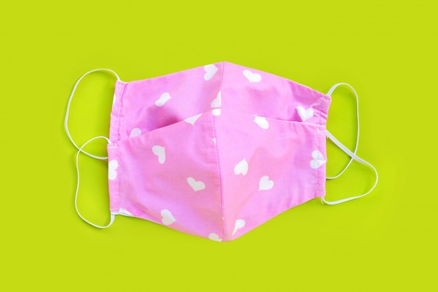 Handmade pink and heart shape cloth masks on green background.