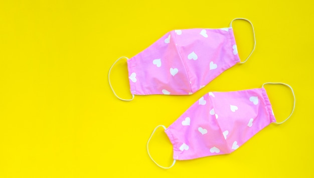 Handmade pink and heart shape cloth masks on yellow background.