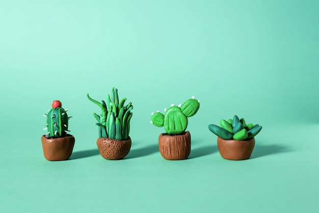 Handmade plasticine green cactuses and succulents in a pots.