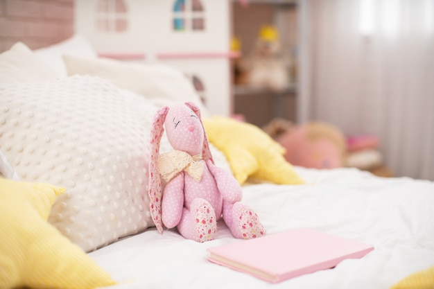 Handmade plush rabbit made of fabric sits on a cozy bed in the children 's room.
