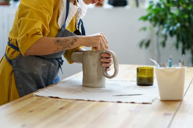 수제 도자기 제조 과정 여성 예술가는 스튜디오에서 도구를 사용하여 원시 점토 주전자를 만듭니다.