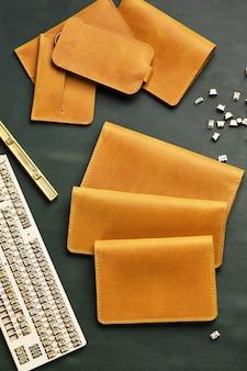 Изделия ручной работы из натуральной желтой и красной кожи. кожаная обложка на паспорт, кожаный кошелек. кожаные изделия для мужчин. вид сверху.