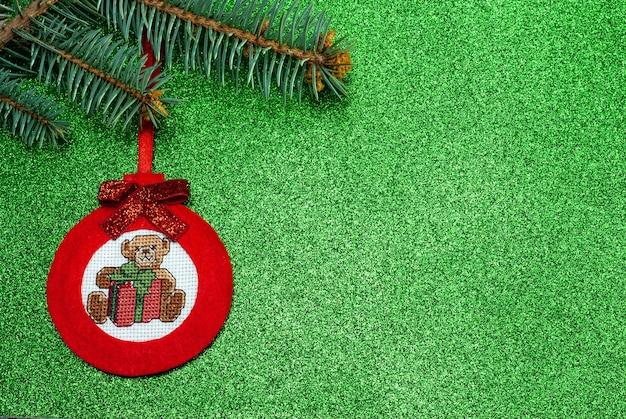 녹색 배경에 십자수 테디베어가 있는 공 형태의 펠트로 만든 수제 빨간 크리스마스 트리 장난감